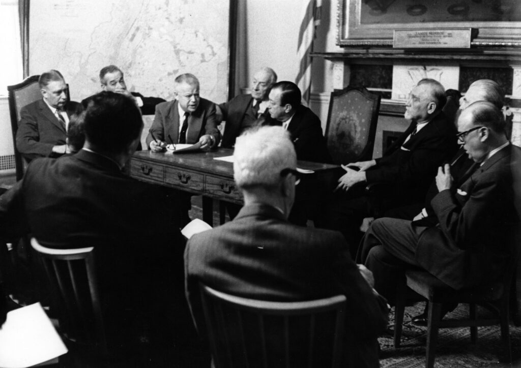 An old-fashioned committee meeting of men around a table